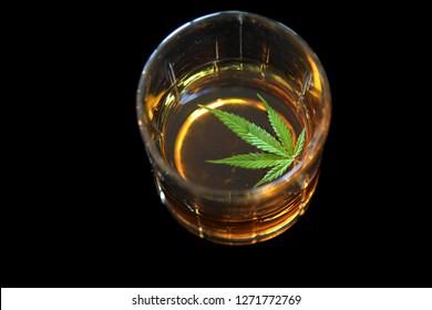 Whiskey with a Marijuana Leaf. Black Velvet background.  Cannabis Liquor.