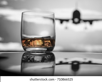 Whiskey on ice at the airport, selective color amber, jet taking off under overcast sky.