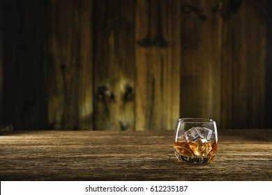 whiskey on the rock on old wood table and wood background