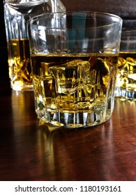 Whiskey on the rocks on a dark wood table and background