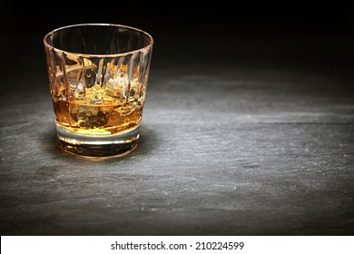 Whiskey on the rocks in a glass tumbler standing on a bar counter in the shadows with a highlight over copyspace or a place for product placement