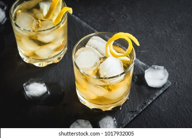 Whiskey on the rocks with lemon peel. Whiskey with ice garnished with citrus twist served on black stone background, top view, copy space.