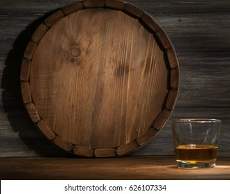 whiskey on a wooden background in the darkness, drawn by light and the barrel