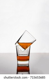 Whiskey, rum or cognac in two glasses on the table with reflection. Concept: luxury alcohol.