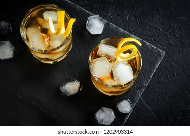 Whiskey or Rum on rocks with lemon twist on black stone background, top view, copy space.