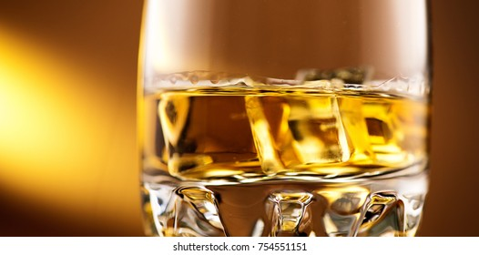 Whiskey, Rum. One glass of Whisky with ice, close-up. On amber color background. Macro shot of Alcohol drink, spirits