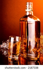 Whiskey, scotch whiskey , tilt shot glass of whiskey and whiskey bottle.Silver Christmas garland at the back and warm color background light.