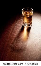 Whiskey shot in a dark bar.