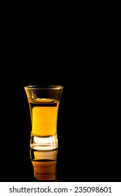 Whiskey in a shot glass isolated on black background