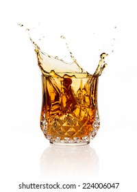 Whiskey splash on elegant glass of cut glass isolated on white background.