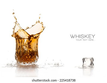Whiskey splash on elegant glass of cut glass and one ice cube melting in foreground. Still life isolated on white background with sample text