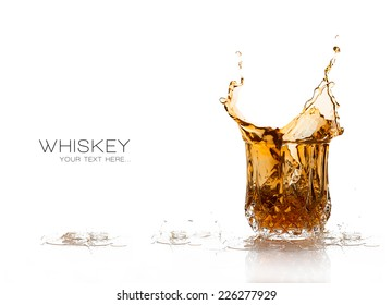Whiskey splash on elegant glass of cut glass isolated on white background with sample text