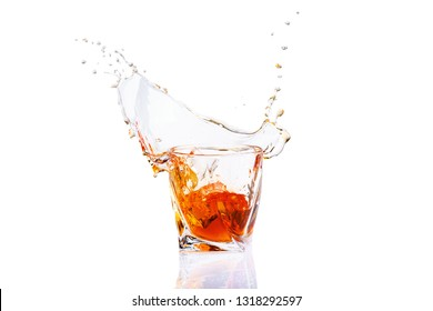 Whiskey with splash on white background, brandy in a glass