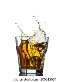 whiskey splashing in glass isolated on white