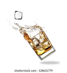 Whiskey splashing out of glass, isolated on white background