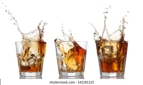 whiskey splashing out of glass isolated on white set