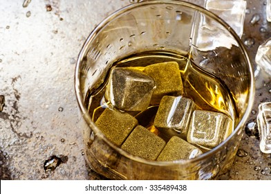 Whiskey stones in glass and ice on black background