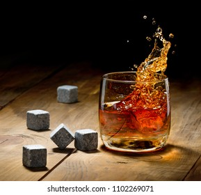 Whiskey and whiskey stones on a wooden table.