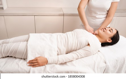 Whiskey swaddling to remove cellulite on female body. Asian woman relaxing during anti-cellulite bandage wrap procedure