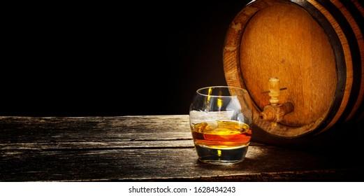 Whiskey tasting, whiskey glass on a whiskey barrel, dark background