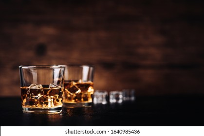 Whisky, bourbon or cognac with ice cubes on black stone table and wood background