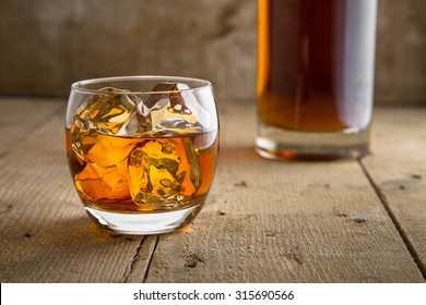 Whisky glass and bottle golden brown ice on wooden surface in saloon bar pub