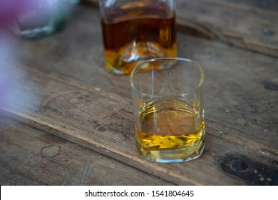 Whisky glass and bottle one used wooden shabby furniture with colourful reflections
