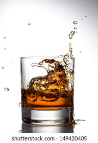 Whisky splashing out of glass on a white background