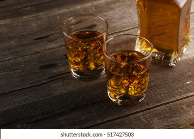 Whisky in two glasses on a dark wooden background. Toning.