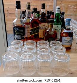 Whisky (whiskey) bottles of various brands, and clean, empty whisky glasses lined up on wooden table at drinks party. Photographed September 2017.