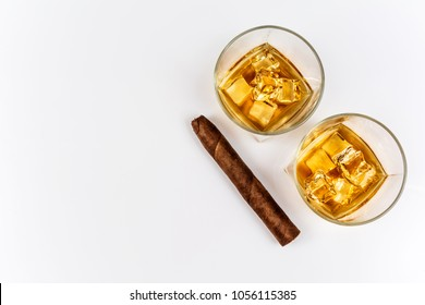 Whisky or whiskey or bourbon with ice and cigar on white background top view