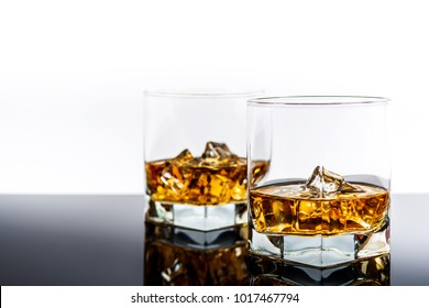 Whisky or whiskey or bourbon with ice on back reflection background