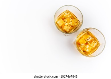 Whisky or whiskey or bourbon with ice on white background top view