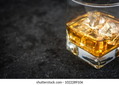 Whisky or whiskey or bourbon with ice on dark stone table