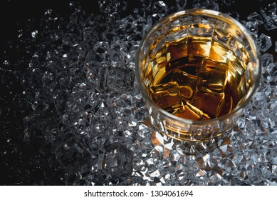 Whisky or whiskey or bourbon with ice on ice background.
