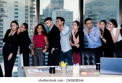 Whisper business.Business team stand in a row and tell a secret to their colleague at office and city scape background.Woman and man trying to hear what thair colleagues saying and standing in a row.T