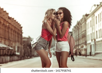 Whispering in ear. Delightful dazzling nice-appealing charming slim fair-haired young-adult lady whispering in ear of her curly-haired Afro-American charming girlfriend wearing eyeglasses outdoors.
