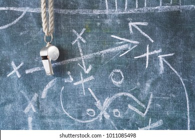 whistle of a soccer or football referee / coach on black board with tactical diagram
