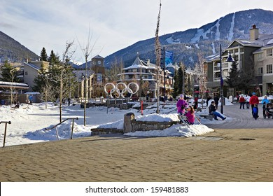 WHISTLER VILLAGE, BRITISH COLUMBIA - FEB 10: Tourists roaming Olympic Village, Whistler, British Columbia, on February 10, 2013 with views of Whistler and Blackcomb Mountain behind the village.