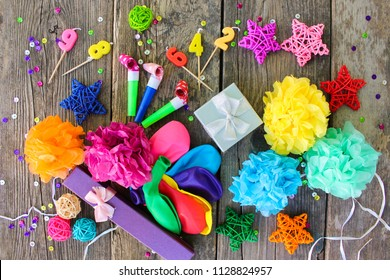 Whistles, balloons gifts, candles, decoration on old wooden background. Concept of children's birthday party. Top view, flat lay.