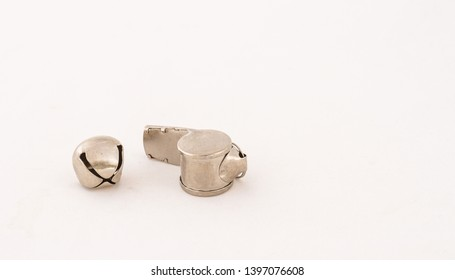 Whistles and a silver bell isolated on a white background image in landscape format with copy space