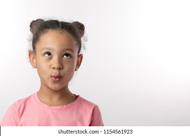 whistlying girl looking up.indifference concept.close up portrait. isolated white background. copy space. kid is ignoring parents, friends.lie and falsehood concept