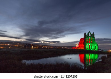 Whitby Abbey during the october Illuminations, perched high upon Whitby West Cliff. Reflection into the Abbey Pond, with the last glimpse of the Yorkshire Sunset.