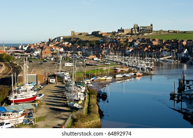 Whitby Abbey on cliff with boats and town and copy space.