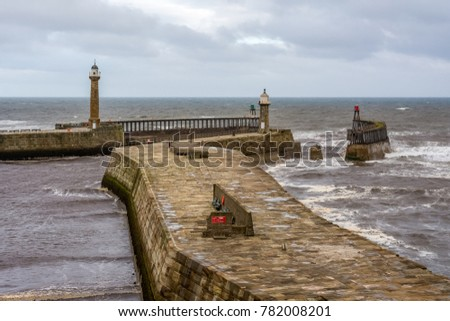 Whitby east and west pier lighthouses and harbour entrance beacons in the historical tourist resort of Whitby, North Yorkshire, England.