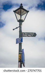 WHITBY, ENGLAND - APRIL 18: A lamp post with a sign for St Mary's Church and Whitby Abbey, in Whitby, North Yorkshire, England. On 18th April 2015.
