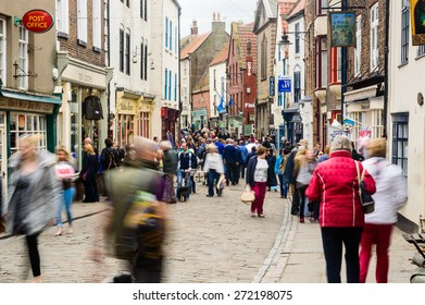 WHITBY, ENGLAND - APRIL 18: People shopping on Church Street, in Whitby, North Yorkshire, England. On 18th April 2015.