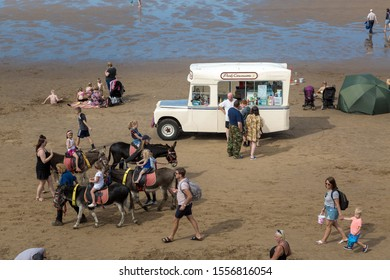 WHITBY, ENGLAND,  UNITED KINGDOM - 08 AUGUST 2019: Traditional landrover icecream van on the beach. Children also enjoy a donkey ride