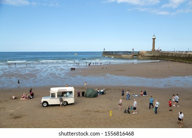 WHITBY, ENGLAND,  UNITED KINGDOM - 08 AUGUST 2019: Traditional landrover icecream van on the beach. Popular for tourists and visitors
