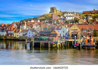 Whitby harbour Yorkshire 12 December 2017 showing Life boat station and Whitby friendship rowing club with St Mary's parish church.